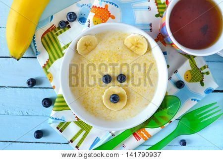 Kids breakfast porridge with fruits and berries face bears