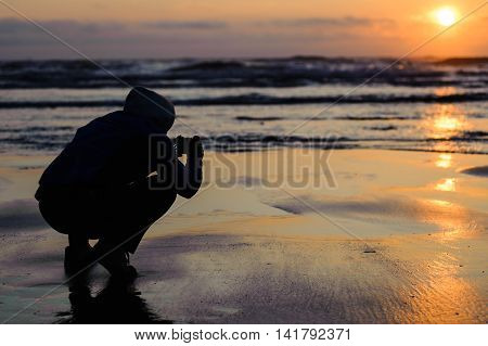 Cape Lookout Oregon USA - July 14, 2009 : man silhouette taking picture at sunset in Cape Lookout, Oregon