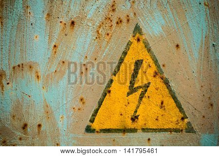 Sign Electrical Hazard Placed On Rusty Metal Panel.