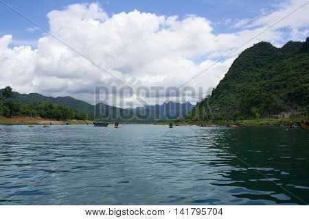 Son river which leads to the Phong Nha Cave in Phong Nha-Kẻ Bàng National Park Central Vietnam. View of stream and mountains in the background.turquoise water. Sunny summer picture with clouds.