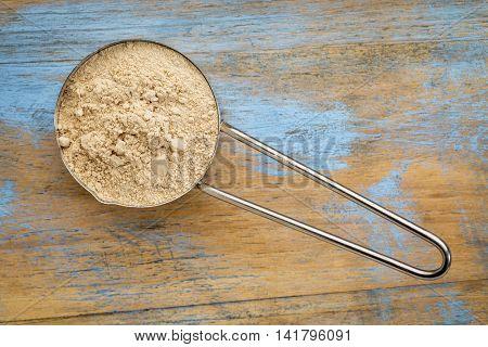 maca root powder on a metal measuring scoop against painted wood