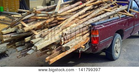 back of maroon pickup truck overloaded with salvaged lumber and posts for new construction work, Songkhla, Thailand