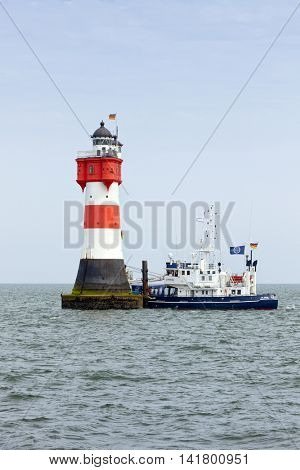 Roter Sand, Germany - July 20, 2014:Supply ship moored at Roter Sand Lighthouse. Roter Sand lighthouse was the first building ever to be erected directly on the sea floor.