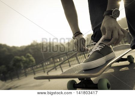 one young skateboarder tying shoelace on skateboard