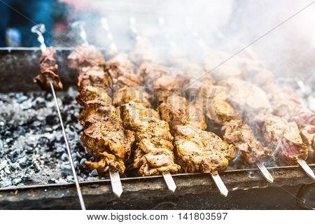 fleshy kebab roasting on mangal with smoke