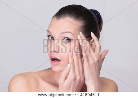 Woman examining her face and wrinkles that can appear, isolated