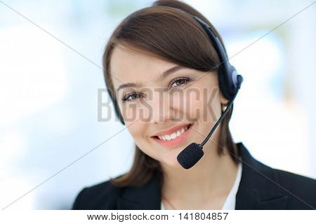 Happy young woman working at callcenter, using headset
