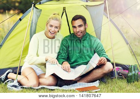 Picture showing couple camping in forest with map