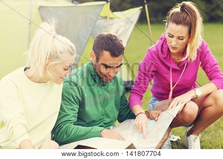 Picture showing group of friends camping in forest and looking at map