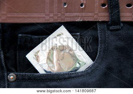 Sexual Health Concept - Close Up Condom On Black Jean