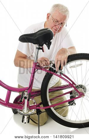 A senior man kneeling as he fixes his granddaughter's bike's brakes.  On a white background.