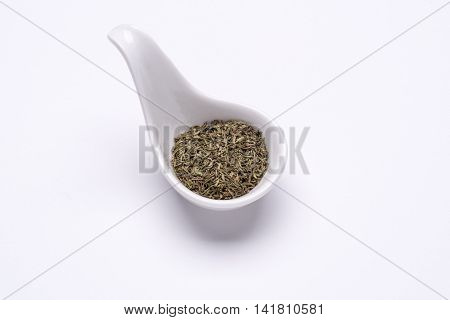 Monotone dry Thyme 1 tablespoon in a white spoon on the white background