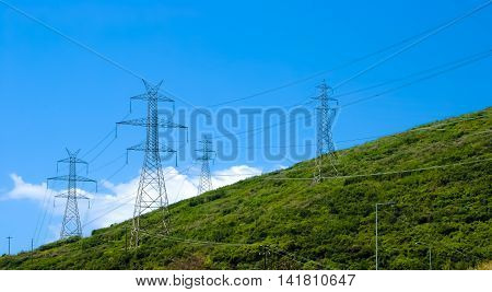 horizontal image of an electricity pylon on the mountain and the blue sky