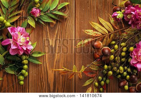 colorful leaves, pumpkin, nuts, apples and mushrooms on wooden background