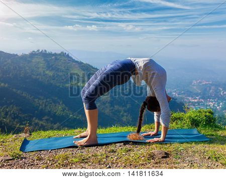Yoga outdoors - young sporty fit woman doing Ashtanga Vinyasa Yoga asana Urdhva Dhanurasana  - upward bow pose - in Himalayas mountains in the morning  Himachal Pradesh, India