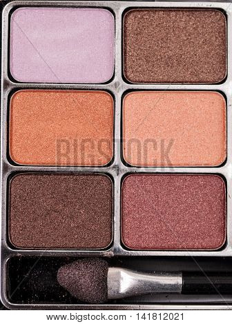 Tan, orange, purple, lilac and brown eye shadow powder in a makeup case