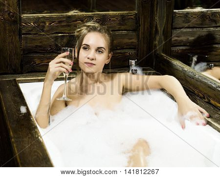 naked young smiling woman with long hair and straight slim beautiful body lying in white bath tub indoor on wooden background. Young woman drinks a champangne.
