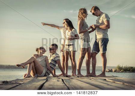Friends sitting on wooden pier under sunset light.
