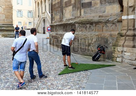 Bergamo, Italy - June 18, 2016: Man playing Street golf during an official tournament in Citta Alta (historic city) of Bergamo. Urban golf is a game, derived from the original game of golf.
