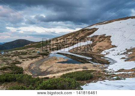 Mountain Lake in the spring. Morning landscape. Last snow on the hills. Reflection of the sky in water. Carpathians, Ukraine, Europe