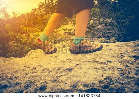 Closeup Of Boy's Feet On The Rock In The Forest.
