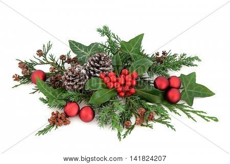 Christmas decoration with red baubles, holly, ivy, snow covered pine cones and winter greenery over white background.