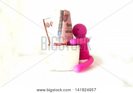 Puppet embrace Thai money on white background