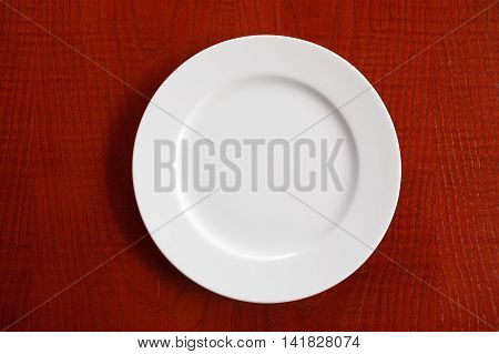 empty clean white plate on wooden table