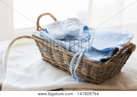 clothing, babyhood, motherhood and object concept - close up of white baby bootees with pile of clothes and towel for newborn boy in basket on table