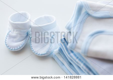 clothing, babyhood, motherhood and object concept - close up of white baby bootees with pile of clothes for newborn boy