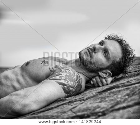 Handsome muscular shirtless man on the beach lying on rocks, looking up to the sky
