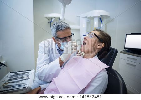 Dentist examining a woman with tools in dental clinic