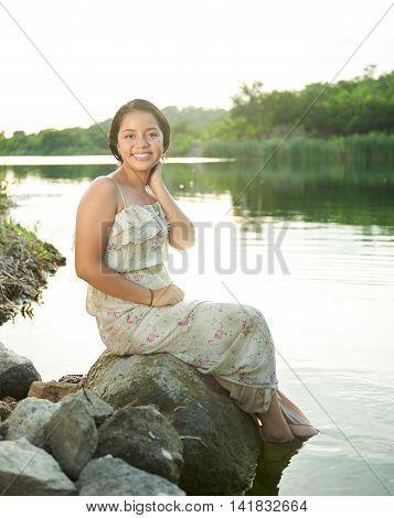 Smiling Girl Sitting On Rocks