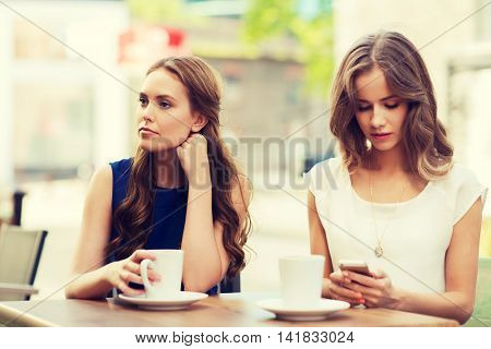 technology, internet addiction, lifestyle, friendship and people concept - young women or teenage girls with smartphones and coffee cups at cafe outdoors