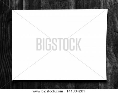 Blank white paper on blurred of black wooden background