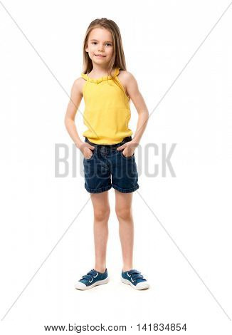cute smiling little girl in yellow shirt, shorts and gumshoes isolated on white background