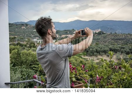 Handsome young man taking photo with cell phone of the landscape