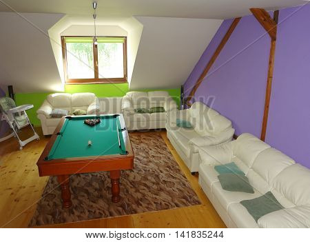 Lubica PRESOV SLOVAKIA - JULY 07 2016: The interior of room with two white divans billiard-table and window in slovakian house in Lubica village Kezmarok High Tatras.