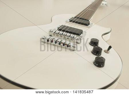 Horizontal, white coloured  electric guitar, white background