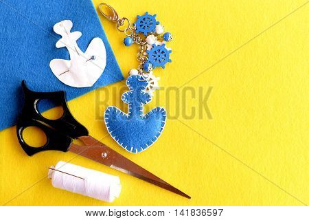 Felt anchor keychain, scissors, thread, pins, paper pattern, blue felt piece on yellow background with empty place for text at right side. Handicrafts concept. Home made key chain for car or bag