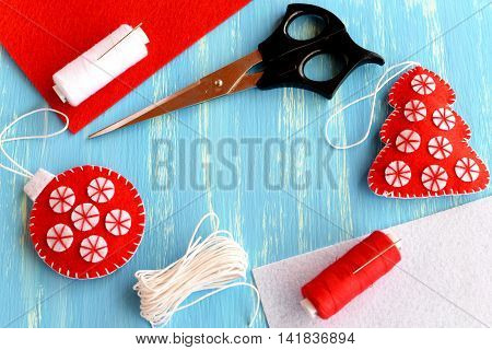 Christmas tree and ball, scissors, thread, needle, flat pieces of felt on a blue wooden background with empty place for text. Sewing set to create Christmas ornaments. Holiday crafts. Top view