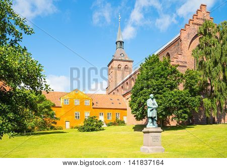 Odense the gothic St. Canute's Cathedral with the Hans Christian Andersen monument in the foreground