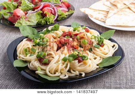 Closeup Black Plate With Pasta And Slices Of Braised Chicken