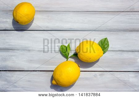 Three lemons on the white wooden background