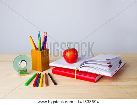Back to school background with books, pencils and red apple over wooden table
