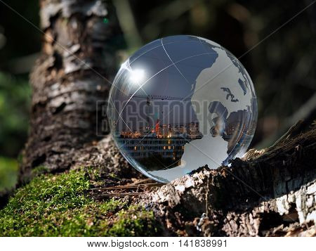 Ball Sphere in the woods on moss. Reflection - a city evening crane windows of houses. The concept of urban ecology construction nature protection