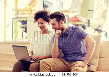 business, startup and people concept - happy creative team with laptop computer in office
