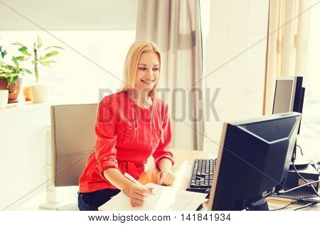 business, startup and people concept - happy businesswoman or creative woman with computers writing to notebook at office
