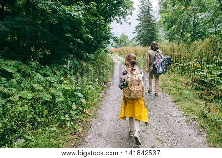 Hikers with backpacks walking in the forest, father with child