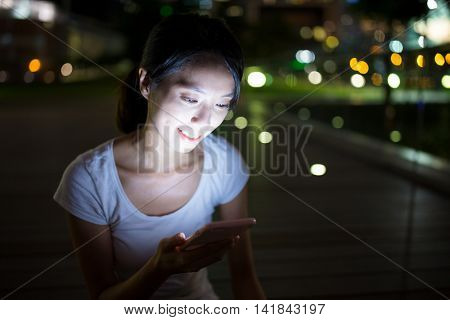 Woman using mobile phone at night